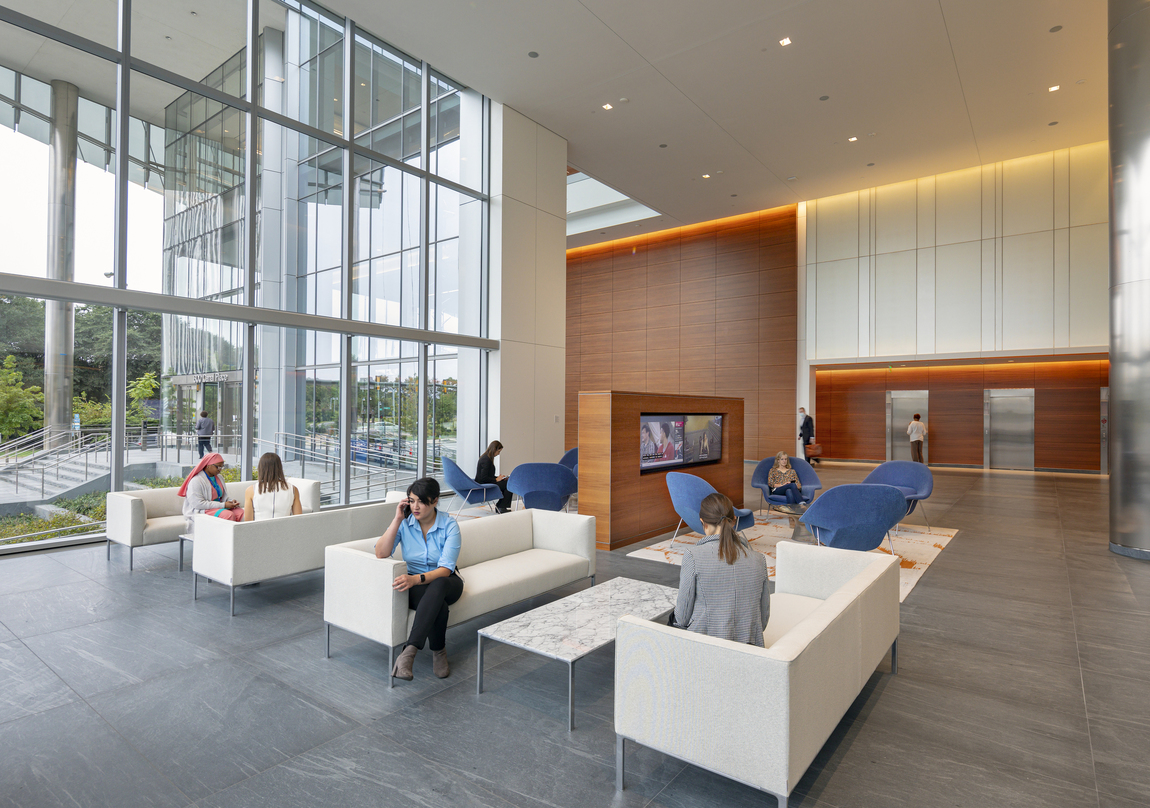 People sitting inside the glass frame walls of the 20-storey 600 Canal Place located in Richmond, Virginia.