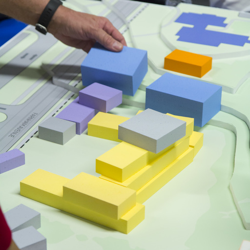 Employees stacking 3d designs on a 2d plan at their workplace.