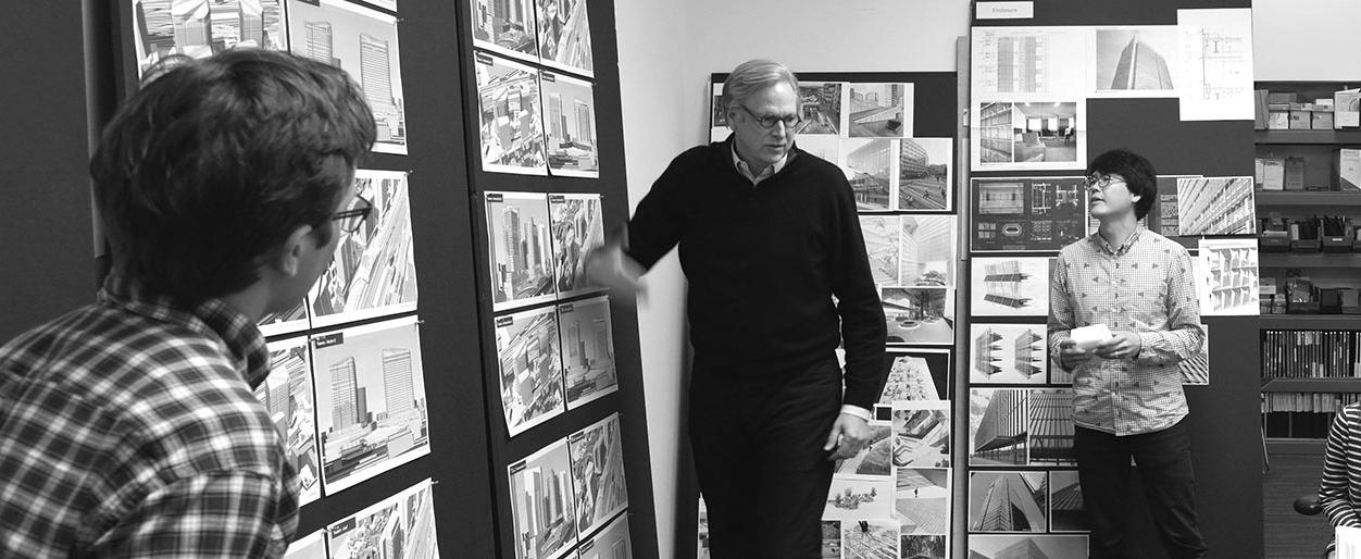 William D Chilton discussing the prospects of various designs pinned on a board with his colleagues.