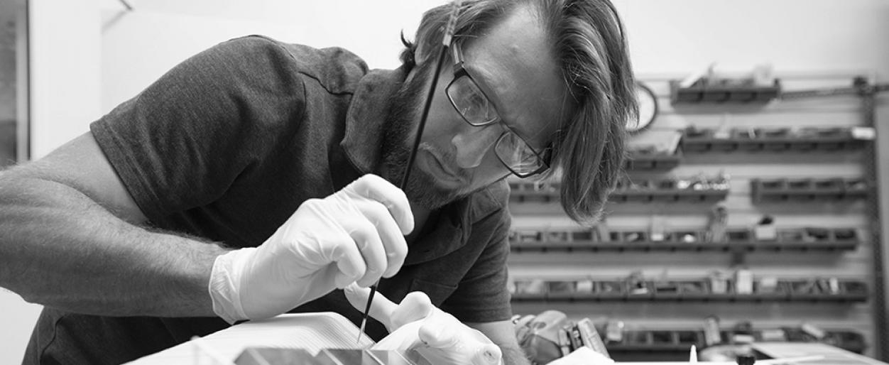Andrew Ostrowitz working meticulously on one of our miniature designs with a brush, wearing gloves