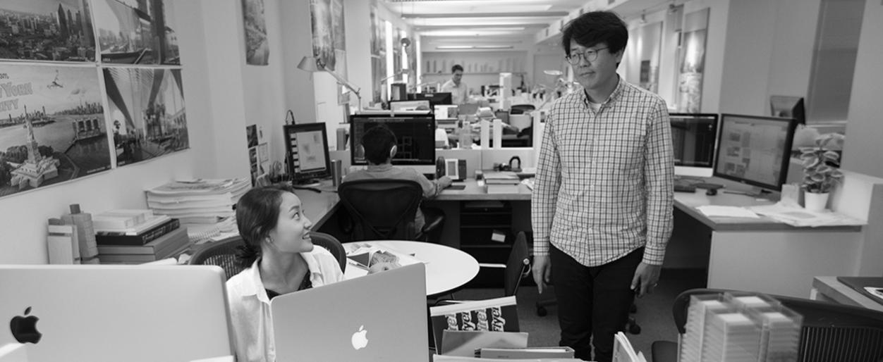 Seung Hwan Namgoong is having a word with Ashley Kim while she works on her computer..