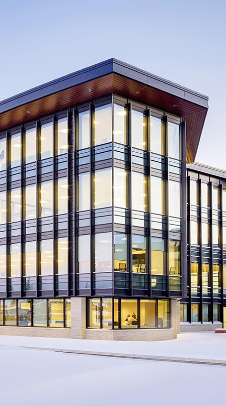 The tall, vertical wood fins and deep roof eaves are tuned to maximize views while optimizing the natural light into the office buildings. The textured fins resemble the tall prairie grasses found throughout the plains.