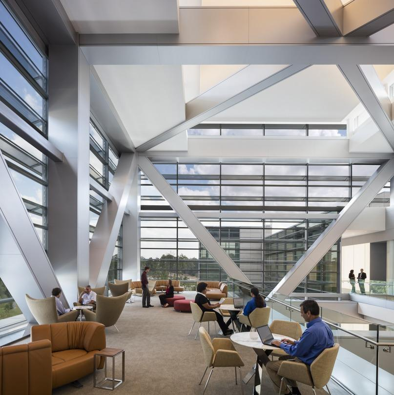 People spending their leisure time inside the ExxonMobil Energy Center surrounded by V shaped pillars and glass frame walls.