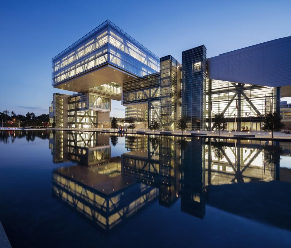 The glass lighted exterior design of the ExxonMobil Energy Center located in Houston, Texas projecting its reflection.