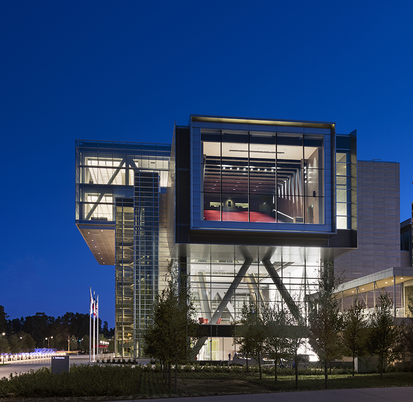 Exterior view of the ExxonMobil Energy Center with glass frame walls and adequate greenery around it.