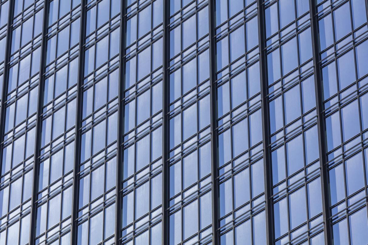 A close up view of the 300 Colorado building which shows the iron railings and glass of the wall