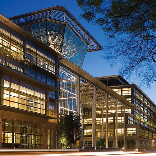 The exterior view of a lighted CalPERS Headquarters Complex that incorporates sunshades, light shelves, and greenery.