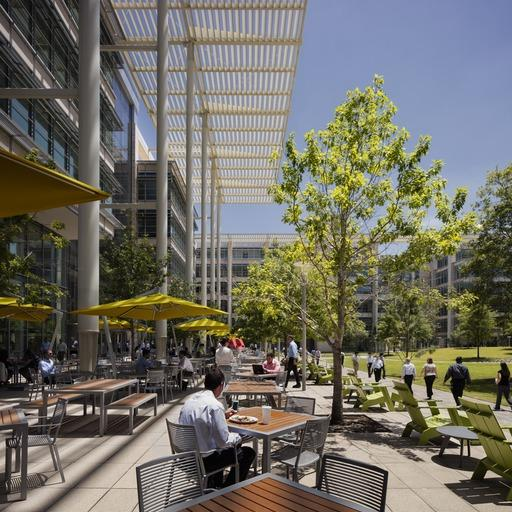 Employees spending their leisure time in a cafeteria outside the ExxonMobil Office Complex with adequate greenery.