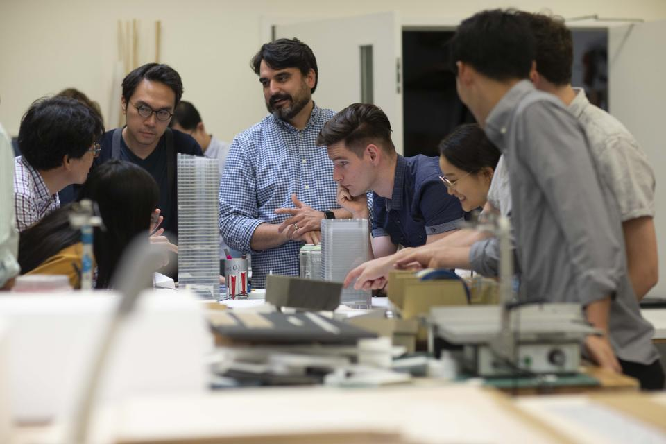 Pickard Chilton employees discussing miniature designs of a project.