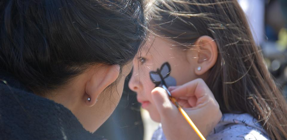 Woman face-painting a blue colored butterfly on a Asian woman's face.